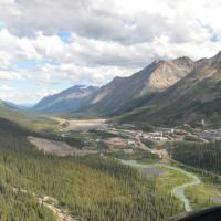 Broad mountain valley, right side forested, cloudy blue sky, townsite with curving dirt roads in valley.