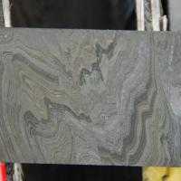 Split face of NQ drill core showing intensely folded then faulted grey, dark grey, and yellow-grey laminations