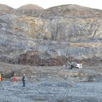 Dudes in an open pit, bit of blue sky, benches of rock are reddish grey, yellowish grey and grey, small drill rig midground right