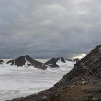 From the air, over half is grey-clouded sky, barren rocky hill foreground right, flat white/grey glacier surface foreground, sharp brown peaks beyond