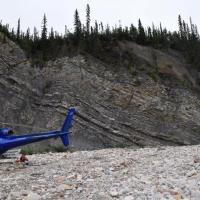 helicopter on gravel near rock cliff