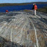 folded metamorphic rock with lake in the background